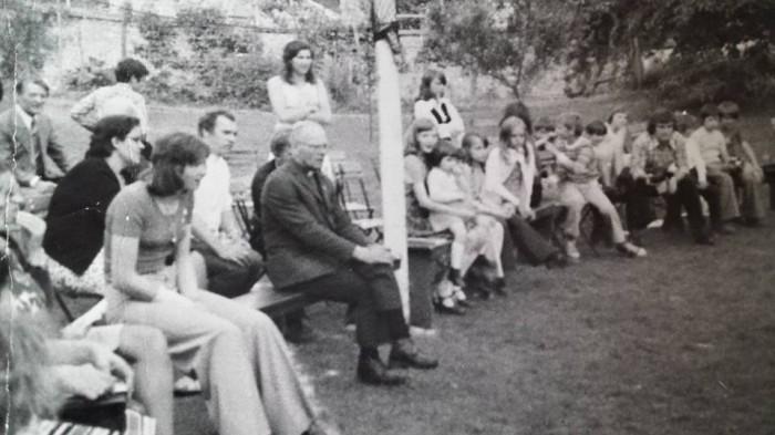 0166 : COMBLAIN-LA-TOUR : Autour de l'ognisko : Mr Jozeph Rzemieniewski ; Annie Nowicki ; Ks Kurzawa ; Pelagie Nowicki ;  À droite du mât : Fabienne Laffut qui materne ses tout-petits dont peut-être Betty Nowicki avec de longs cheveux et plus à droite : Henry Bogdanski de la région du Centre.